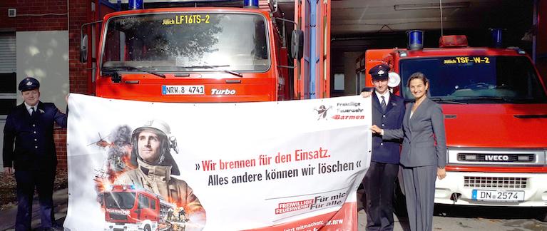 Patricia Peill (MdL) unterstreicht mit der Übergabe des Werbebanners an die Barmener Feuerwehr ihre Wertschätzung und Unterstützung des Ehrenamts. Foto: PPP